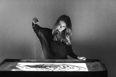 Die Frau zeichnet auf Sand, Sandanimation, Sand gießt aus seinen Händen Lizenzfreie Stockfotos