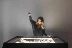 Die Frau zeichnet auf Sand, Sandanimation, Sand gießt aus seinen Händen Stockfotos