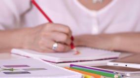 Die Frau zeichnet in ein Notizbuch färbte Bleistifte Die Frau arbeitet an der Tablette stock video