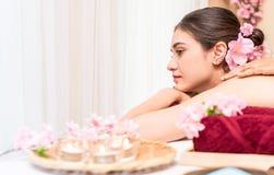 Die Frauen, die auf einem Badekurort liegen, gehen mit Blumenkerzen zu Bett Stockbild