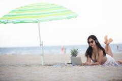 Die Frauen, die Bikinis tragen, benutzen Laptop für Arbeit und hören auf m stockfotos