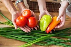 Die Frauen, die Abendessen in einer Küche hält das Gemüse vorbereiten, übergibt nährendes gesundes Lebensmittel zu Hause kochend Lizenzfreie Stockfotos