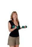 Die Frauen, die bicep tun, kräuselt sich mit freien Gewichten Stockfoto
