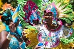 Die Frauen, die durchdachte mit Federn versehene Kostüme tragen, feiern karibische Kultur stockfoto