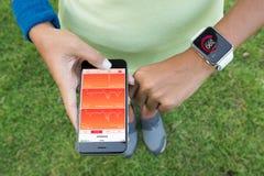 Die Frauen, die iphone 6s und Apfeluhr verwenden, überprüfen Gesundheits-APP Lizenzfreie Stockbilder