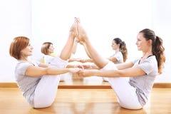 Die Frauen, die Körperbalance finden, werfen eine phisical Übung Lizenzfreie Stockbilder