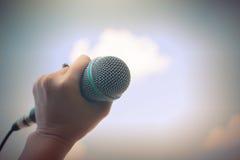 Die Frauen, die Mikrofon mit instagram halten, mögen in der Querverarbeitung Stockbild