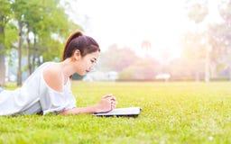 Die Frauen ist auf dem Gras und schön sie ein Buch lesend stockbilder