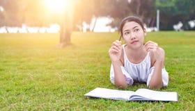 Die Frauen ist auf dem Gras und schön sie ein Buch lesend lizenzfreie stockfotografie