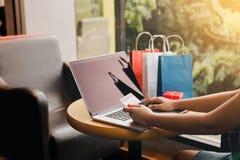 Die Frauen, die Laptop für online kaufen verwenden und erwerben Punkte zum websit lizenzfreies stockbild