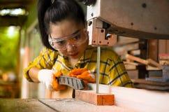 Die Frauen-Stellung ist das Handwerk, das geschnittenes Holz an einer Werkbank mit Bandsägeelektrowerkzeugen an der Tischlermasch lizenzfreie stockbilder