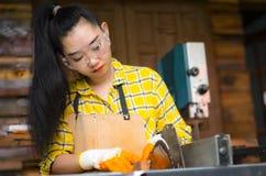 Die Frauen-Stellung ist das Handwerk, das geschnittenes Holz an einer Werkbank mit Kreissägeelektrowerkzeugen an der Tischlermasc stockbild