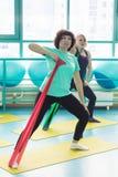 Die Frauen, die Turnhalle tun, trainiert mit Latexeignungsbändern Stockbild