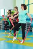 Die Frauen, die Turnhalle tun, trainiert mit Latexeignungsbändern Lizenzfreies Stockfoto