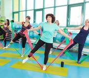 Die Frauen, die Turnhalle tun, trainiert mit Latexeignungsbändern Lizenzfreie Stockfotos