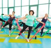 Die Frauen, die Turnhalle tun, trainiert mit Latexeignungsbändern Lizenzfreie Stockfotografie