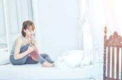 Die Frauen, welche die grauen Pyjamas sitzen auf der Couch tragen, benutzen den Griff zum Fuß lizenzfreie stockfotografie