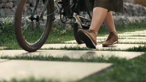 Die Frauenbeine, die neben Reiten gehen, fahren auf Stadtstraße rad Frauenfüße und -Fahrradfelge stockbilder