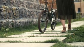 Die Frauenbeine, die neben Reiten gehen, fahren auf Stadtstraße rad Frauenfüße und -Fahrradfelge stockbild