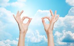 Die Frauenhände, die o.k. darstellen, unterzeichnen vorbei blauen Himmel Lizenzfreie Stockfotos