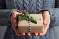 Die Frauenhände, die Weihnachtsgeschenk oder -Präsentkarton halten, verzierten Tannenbaum Gemütlicher Winterschuß Lizenzfreies Stockfoto