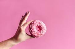 Die Frauenhand, die bunten Donut mit hält, besprüht Stockfotos