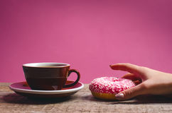 Die Frauenhand, die bunten Donut mit hält, besprüht Lizenzfreies Stockfoto