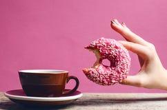 Die Frauenhand, die bunten Donut mit hält, besprüht Lizenzfreie Stockbilder