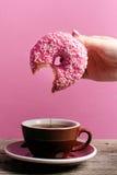 Die Frauenhand, die bunten Donut mit hält, besprüht Stockbild