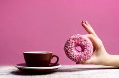 Die Frauenhand, die bunten Donut mit hält, besprüht Stockfoto