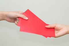 Die Frauenhand, die Rot gibt, schlagen das Enthalten des Geldes ein Lizenzfreie Stockfotografie