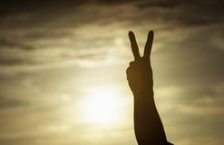 Die Frauenhand, die zwei Finger auf dem Sonnenunterganghintergrund, mit alles Konzept kämpfend anhebt, Leben geht auf Konzept, Si Lizenzfreies Stockfoto