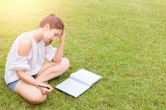Die Frauenkopfschmerzen Die Frauen ist auf dem Gras das Buch ist auf Knie lizenzfreie stockfotografie