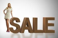 Die Frauenstellung nahe bei Verkaufswort lizenzfreie stockfotografie