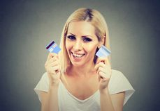 Die freie junge Frau der glücklichen Schuld, die eine Kreditkarte hält, schnitt in zwei Stücke Stockfotos