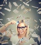 Die freie junge Frau der glücklichen Schuld, die eine Kreditkarte hält, schnitt in zwei Stücke unter Geldregen lizenzfreies stockfoto
