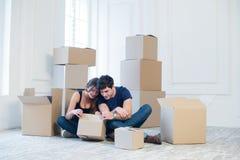 Die Freude am Bewegen in das Haus Ein liebevolles Paar, das herein Kasten hält Stockfoto