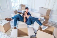 Die Freude am Bewegen in das Haus Ein liebevolles Paar, das herein Kasten hält Stockbild