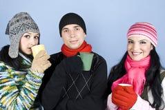 Die Freunde, die ein Cup des heißen Getränks genießen und erhitzen oben Stockfotografie