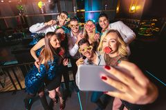 Die Freunde, die in einem Nachtklub partying sind, machen selfie Foto lizenzfreie stockbilder
