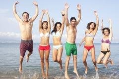 Die Freunde springend auf den Strand mit der Hand oben Lizenzfreie Stockbilder