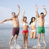Die Freunde springend auf den Strand mit der Hand oben Stockbilder