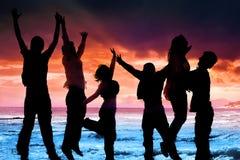 Die Freunde springend in dem Meer Stockbild