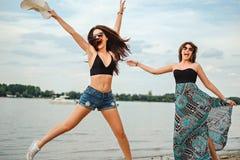 Die Freundinnen springend auf den Strand Stockfoto