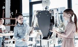 Die freundlichen Kinder, die Menschen besprechen, mögen Roboter Lizenzfreies Stockbild