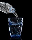 Die Frische, die kühl sind und das saubere Trinkwasser, das zum blauen Glas gießt, ist Stockbild