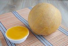 Die frische Melone des Ganzen mit Nuten und Honig in eine Schüssel Stockfotos