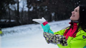 Die frohe Frau versucht, Schneeflocken zu fangen Winter draußen genießend Lustiges Mädchen in hellem buntem Ski Suit und lang stock footage