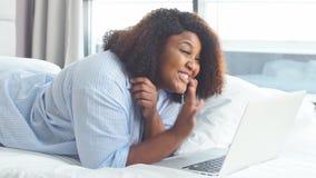 Die frohe pralle Frau, die online mit einem Freund, afrikanische Hausfrau spricht, ist ein Blogger stock video