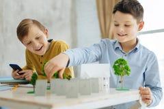 Die frohen jugendlichen Jungen, die an Ökologie arbeiten, steuern Aufgabe automatisch an stockfotos